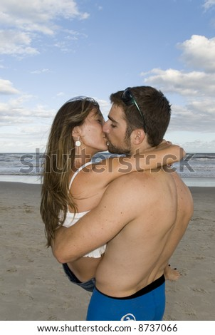 Young healthy couple kissing in the beach. - stock photo