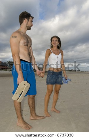 Young healthy couple looking at each other in the beach. Full body shot. - stock photo