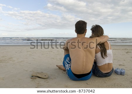 Young healthy couple sited in the sand, looking out into the sea. - stock photo
