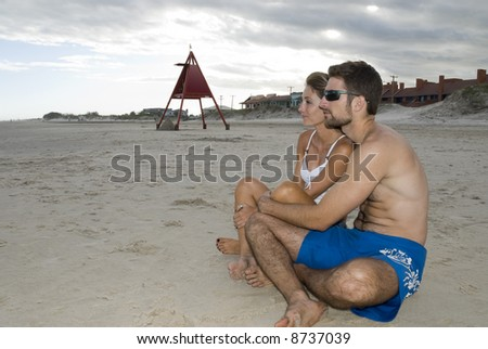 Young healthy couple sited in the sand, looking out into the sea (side shot). - stock photo