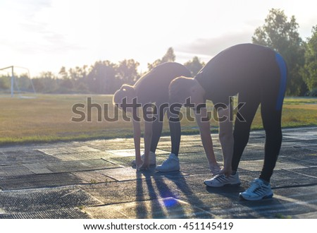 Young healthy couple stretching their legs before running or jogging in park. Workout outdoors - stock photo