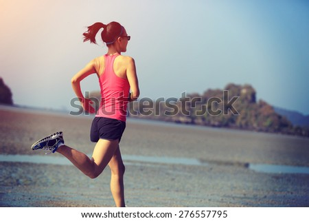 young healthy lifestyle woman running at sunrise beach  - stock photo