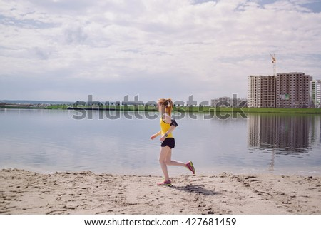Young healthy lifestyle woman running at sunrise beach. Girl running at sand near water on city's beach. Girl running in yellow sports shirt and black shorts - stock photo