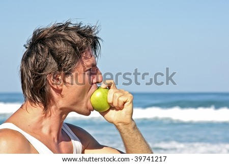 Young healthy man eating an apple at the beach - stock photo