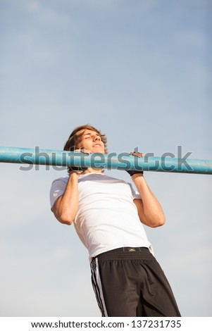 young healthy man making exercise in a public park - stock photo