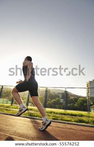 young healthy man run on athletic race sport track and representing concept of sort and speed - stock photo
