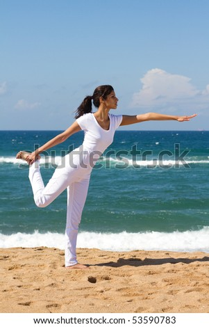 young healthy woman doing yoga on beach - stock photo