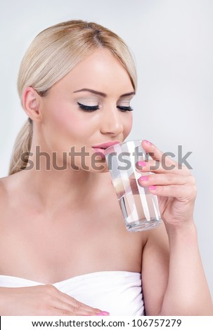 Young healthy woman drinking water - stock photo