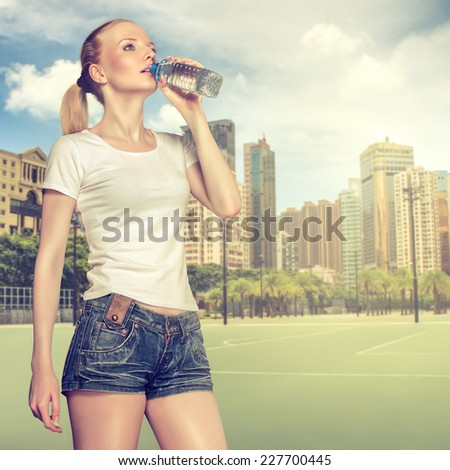 Young healthy woman drinking water while training outdoor - stock photo
