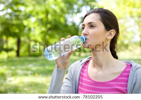 young healthy woman drinks water from bottle, outdoor - stock photo