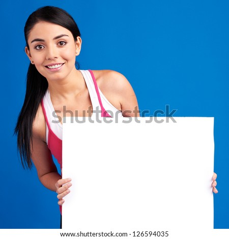 Young healthy woman holding white empty banner for copy space - stock photo