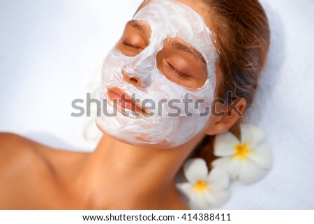 Young healthy woman in tropical spa making treatments and face mask - stock photo