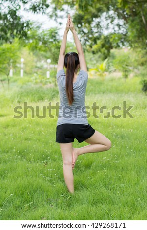 Young healthy woman practicing yoga  in the park.Young people do yoga in the park.