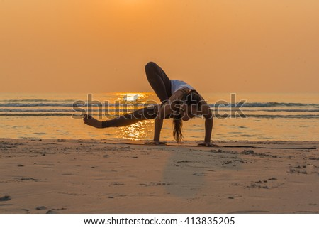 Young healthy woman practicing yoga on the beach at sunrise