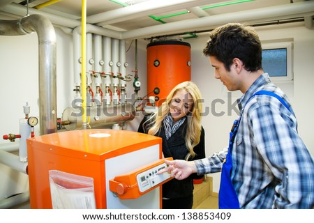 young heating engineer in boiler room for heating system - stock photo