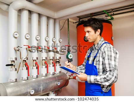 young heating engineers in the boiler room for heating - stock photo
