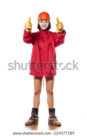 young helmeted woman worker with muddy boots showing thumbs up - stock photo