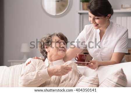 Young helpful caregiver serving hot tea to older woman - stock photo