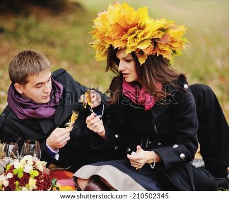 Young heterosexual couple having date in autumn garden. - stock photo