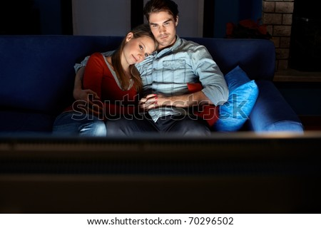 young heterosexual couple hugging on sofa and watching movie on tv at home. Horizontal shape, front view, copy space - stock photo
