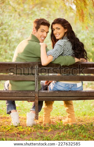 Young heterosexual couple hugging sitting on a park bench, behind their back looking at the camera with a smile on their faces. - stock photo