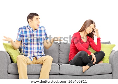 Young heterosexual couple sitting on a sofa during an argument isolated on white background - stock photo