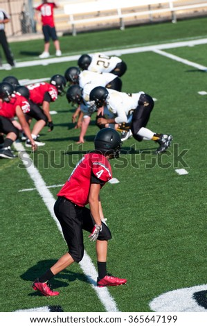 Young high school football player getting ready to go out for a pass on the field. - stock photo