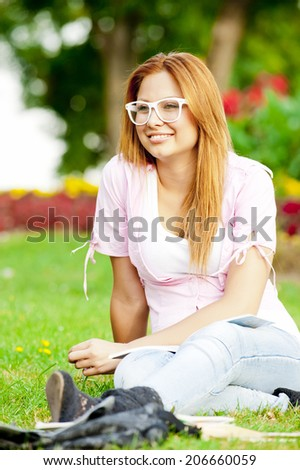 young high school student or college girl learn and sit in the park on the green grass/young college or high school student - stock photo