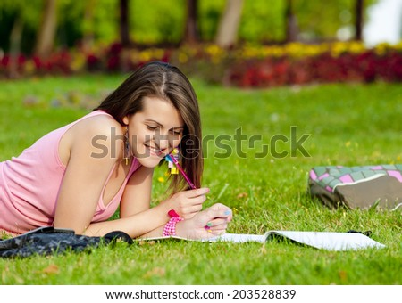 young high school student or college girl lying on the grass in the park and learn/young high school student - stock photo