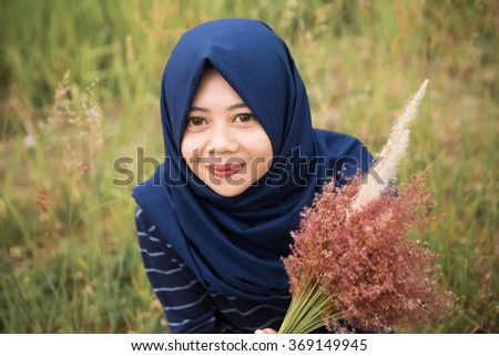 Young hijab woman sitting in the red flower field and smiling