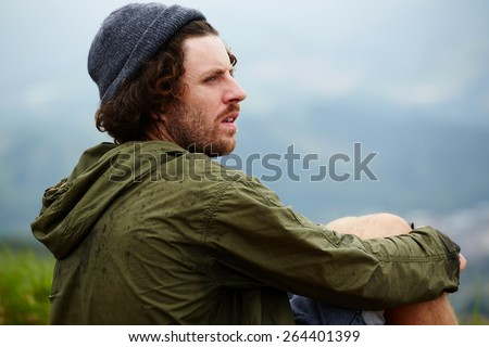 Young hike hipster man sitting at his campsite on the top of hill while enjoying the nature in rainy weather, young man relaxing on the grass enjoying outdoors view and resting after hike way - stock photo