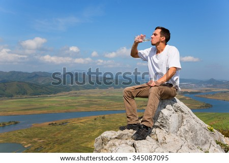 Young hiker drinks water from a bottle on top of the mountain