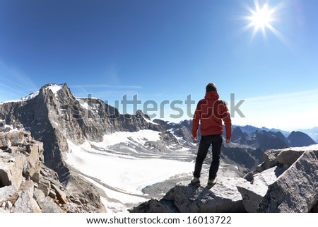 Young hiker enjoying the view over the beautiful landscape of Gran Paradiso National Park, Italy - stock photo