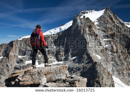 Young hiker enjoying the view over the beautiful landscape of Gran Paradiso peak (4046 mt), Italy - stock photo