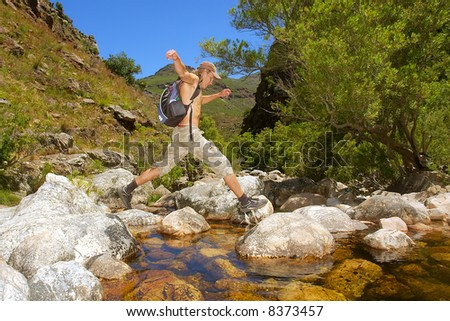 Young hiker jumps across small river in awesome mountains. Shot in the Kromrivier - Du Toitskloof Nature Reserve, near Paarl, Western Cape, South Africa. - stock photo