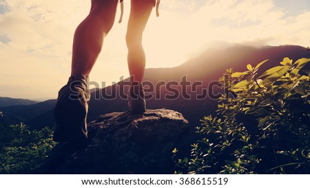 young hiker legs hiking on mountain peak - stock photo