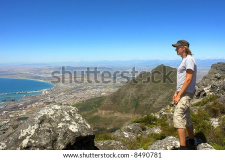 Young hiker looks at port city from mountain. Shot in Table Mountain (cable car area), Cape Town, South Africa.