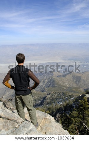 Young hiker man contemplating the breathtaking view atop summit. Amazing view of Joshua Tree National Park and Palm Springs, CALIFORNIA. - stock photo
