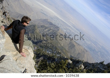 Young hiker man contemplating the breathtaking view atop summit. Amazing view of Joshua Tree National Park and Palm Springs, CALIFORNIA.