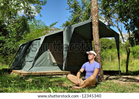 Young hiker meditates under pine tree in camping site. Shot near Sodwana Bay nature reserve, KwaZulu-Natal province, Southern Mozambique area, South Africa.