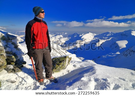 Young hiker standing on the mountain top in sunny winter day - stock photo