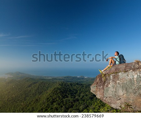 Young hiker standing on top of the mountain at sunny day - stock photo