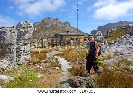 Young hiker stands in front of mountain chalet. Shot in Hottentots-Holland Mountains nature reserve, near Grabouw, Western Cape, South Africa. - stock photo