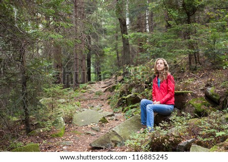 Young hiker woman sitting on a halt in stones among the forest. Hiking in the mountains rise on a forest footpath
