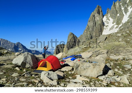 Young hiker woman stretching at a campsite with red tent high in the mountains. - stock photo
