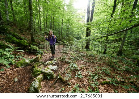 Young hiker woman with backpack on a forest trail in the mountains