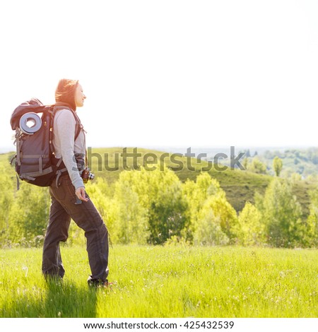 Young hiker woman with backpack standing on summit of hill. Happy girl spending time at outdoors - stock photo