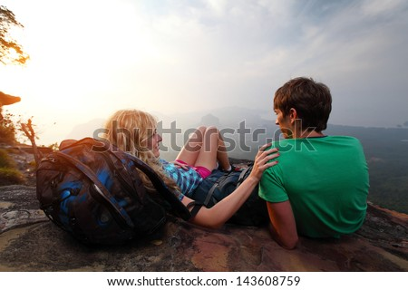 Young hikers relaxing on top of a mountain and enjoying sunrise - stock photo