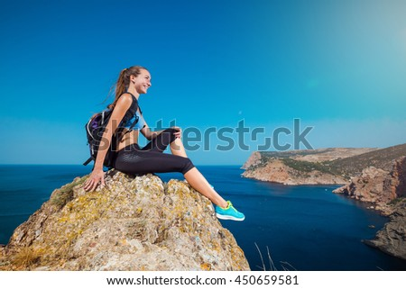 Young hikers woman sitting on a rock and looking at sea and mountain landscape. Happy athlete relaxes on a stone and enjoying the view from the cliff.