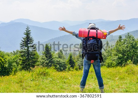 Young hiking woman standing on top of the mountain with valley on the background. Happy young traveler with backpack. - stock photo